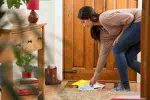 Woman picking up mail from door mat